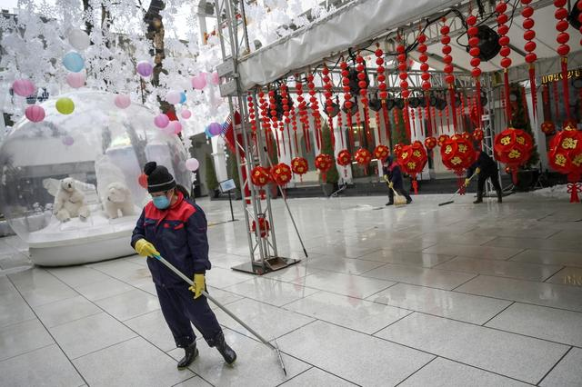 A worker wearing a face mask cleans the ground amid snowfall, following an outbreak of the novel coronavirus in the country, on Valentine's Day at the Sanlitun shopping area in Beijing, China February 14, 2020. REUTERS/Tingshu Wang
