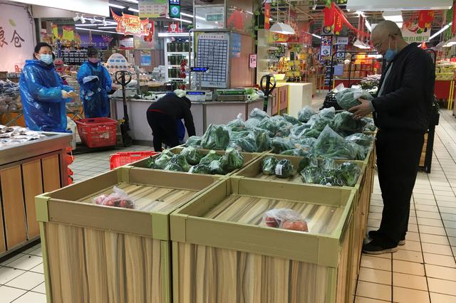 A customer shops for vegetables at a supermarket in Wuhan, the epicentre of the novel coronavirus outbreak, in Hubei province, China February 14, 2020.  REUTERS/Stringer