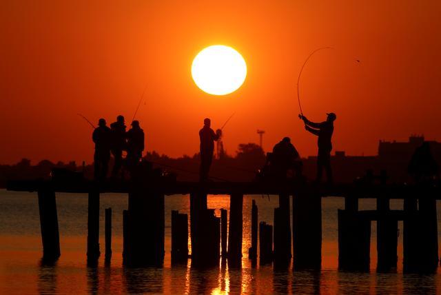 FILE PHOTO: Fishermen gather on a mooring during sunset in Yevpatoriya, Crimea October 23, 2019. REUTERS/Alexey Pavlishak//File Photo