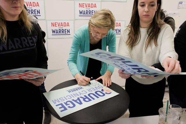 U.S. Democratic presidential candidate Senator Elizabeth Warren autographs a sign for a supporter as she holds a ''Canvass Kickoff'' event at her campaign field office in North Las Vegas, Nevada, U.S. February 20, 2020.   REUTERS/David Ryder