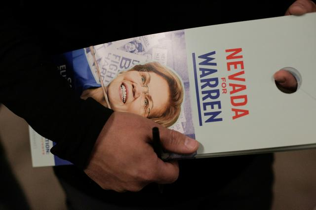 A supporter holds a door hanger while preparing to canvass for U.S. Democratic presidential candidate Senator Elizabeth Warren after she held a ''Canvass Kickoff'' event at her campaign field office in North Las Vegas, Nevada, U.S. February 20, 2020.   REUTERS/David Ryder