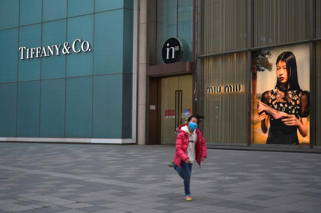 A child wearing a face mask runs past stores of Tiffany & Co and Miu Miu, as the country is hit by an outbreak of the novel coronavirus, in Beijing, China February 20, 2020. REUTERS/Tingshu Wang