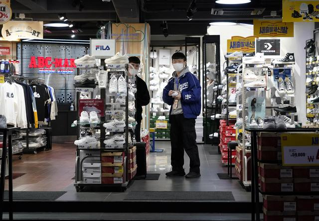 Shopkeepers wearing masks to prevent contracting the coronavirus wait for a customer at Dongseong-ro shopping street in central Daegu, South Korea February 21, 2020.   REUTERS/Kim Hong-Ji