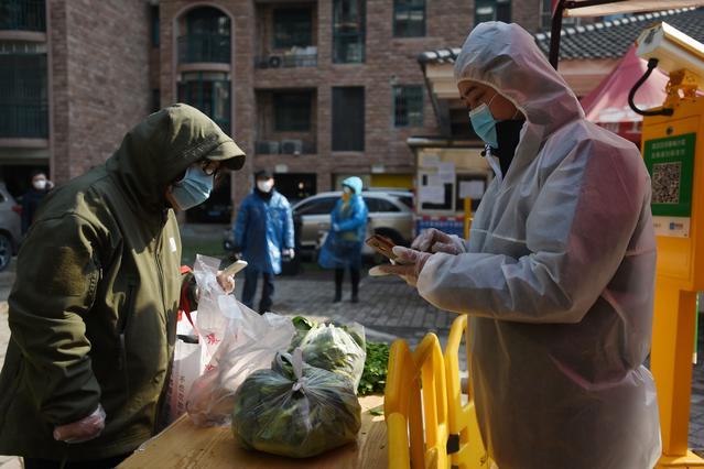 A resident collects vegetables purchased through group orders at the entrance of a residential compound in Wuhan, the epicentre of the novel coronavirus outbreak, Hubei province, China February 21, 2020. REUTERS/Stringer