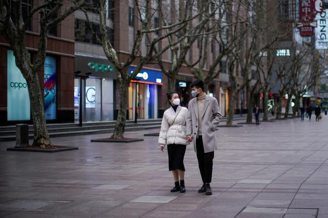 A couple wear masks at a main shopping area as the country is hit by an outbreak of the new coronavirus in downtown Shanghai, China February 21, 2020. REUTERS/Aly Song