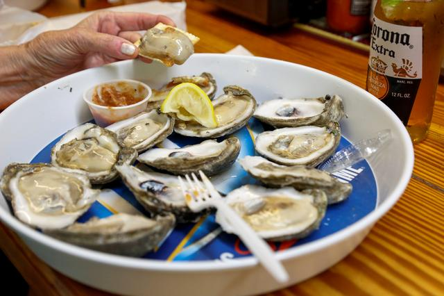 A customer at Lynn's Quality Oysters in Eastpoint, Florida, U.S., eats raw oysters from Texas at the restaurant, which often has to serve oysters from out of state due to the limited oyster production in Apalachicola Bay, February 11, 2020.   REUTERS/Colin Hackley