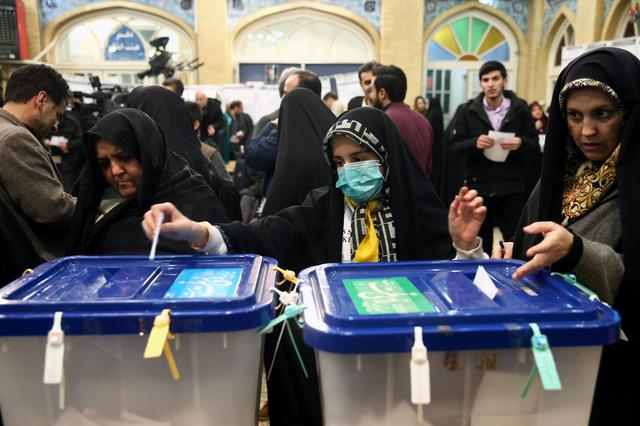 A woman wears a face mask as she casts her vote during parliamentary elections at a polling station in Tehran, Iran February 21, 2020. Nazanin Tabatabaee/WANA (West Asia News Agency) via REUTERS ATTENTION EDITORS - THIS IMAGE HAS BEEN SUPPLIED BY A THIRD PARTY.