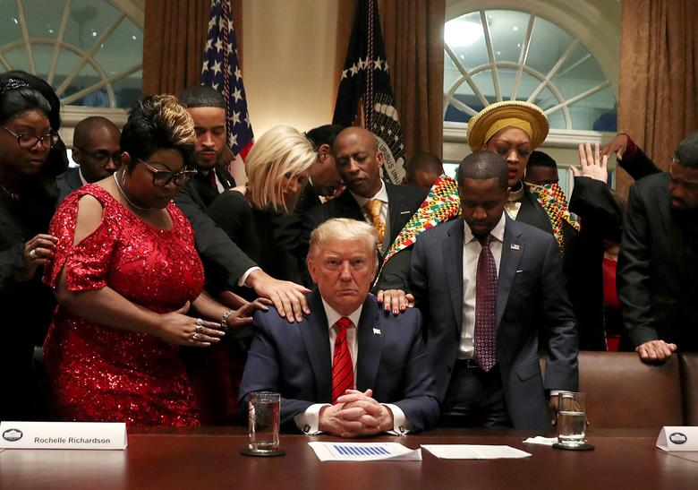 African-American supporters, including Terrence Williams, Angela Stanton and Diamond and Silk, pray with President Donald Trump in the Cabinet Room of the White House in Washington. REUTERS/Leah Millis