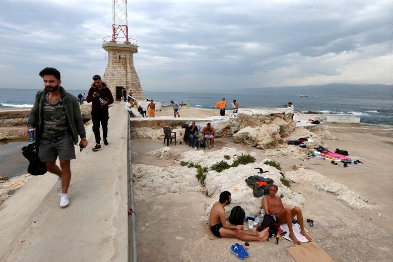 ДО: Мужчины собираются на пляже в Бейруте, Ливан, 12 марта 2020 года. РЕЙТЕР / Мохамед Азакир