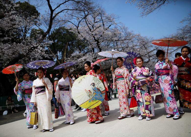 Посетители из-за рубежа в одежде кимоно смотрят на цветение вишни в парке Уэно в Токио, Япония, 22 марта 2020 года. РЕЙТЕР / Иссей Като