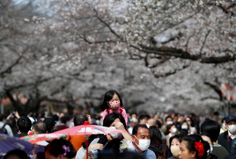 Посетители в защитных масках смотрят на цветущие вишни в парке Уэно в Токио, Япония, 22 марта 2020 года. REUTERS / Issei Kato