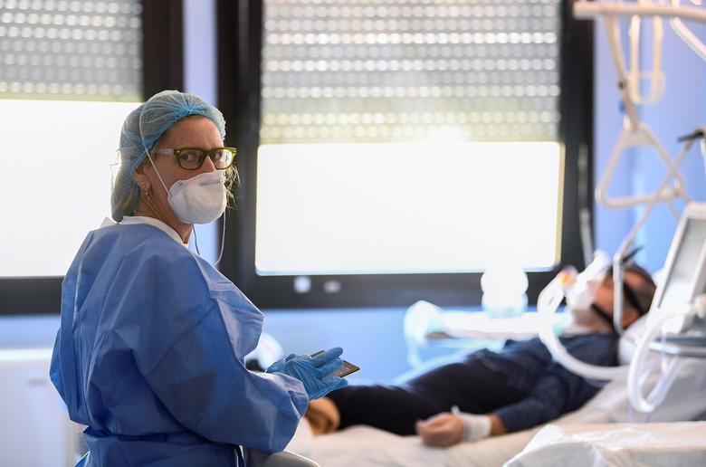 Una trabajadora médica con una máscara protectora y un traje observa mientras trata a un paciente que padece coronavirus en una unidad de cuidados intensivos en el hospital Oglio Po en Cremona, el 19 de marzo. REUTERS / Flavio Lo Scalzo