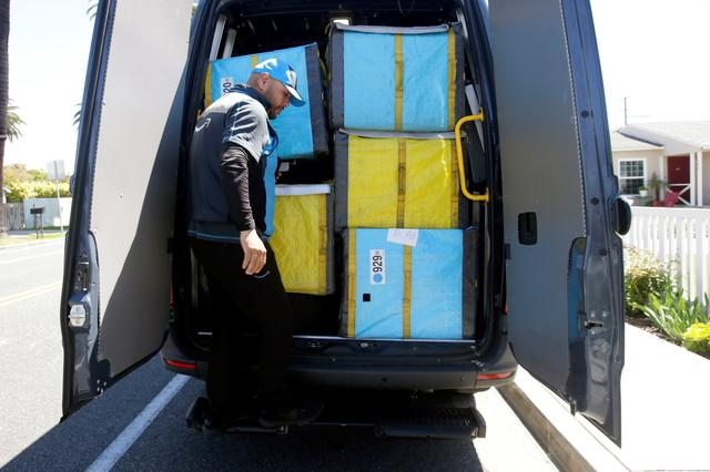 Joseph Alvarado steps down from the back of the van as he makes deliveries for Amazon during the outbreak of the coronavirus disease (COVID-19) in Costa Mesa, California, U.S., March 23, 2020.      REUTERS/Alex Gallardo