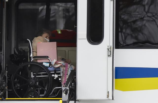 A resident from St. Joseph's nursing home is seen on board a bus while being evacuated by medical officials, after a number of residents tested positive for coronavirus disease (COVID-19) in Woodbridge, New Jersey, U.S., March 25, 2020.  REUTERS/Stefan Jeremiah