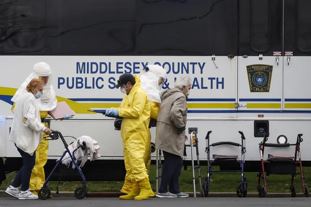 Medical officials aid a residents from St. Joseph's nursing home to board a bus, after a number of residents tested positive for coronavirus disease (COVID-19) in Woodbridge, New Jersey, U.S., March 25, 2020.  REUTERS/Stefan Jeremiah