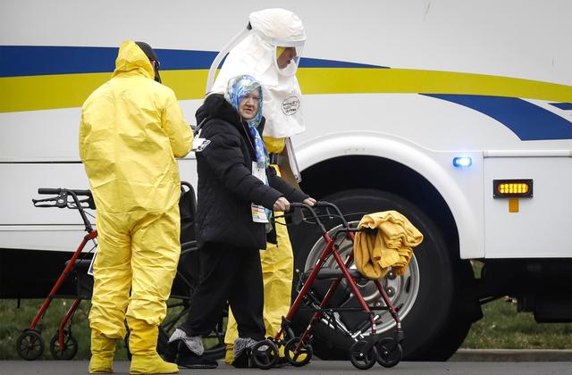 Medical officials aid a resident from St. Joseph's nursing home to board a bus, after a number of residents tested positive for coronavirus disease (COVID-19) in Woodbridge, New Jersey, U.S., March 25, 2020.  REUTERS/Stefan Jeremiah