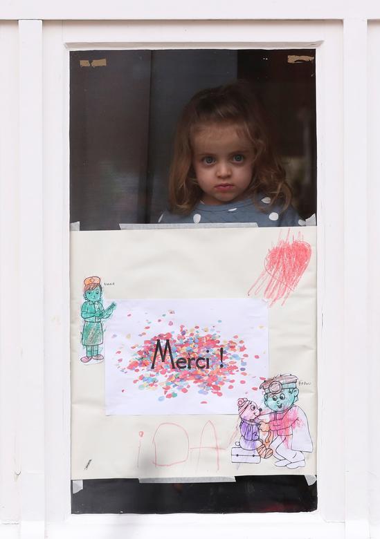 Ида, 4 года, стоит за своим рисунком в честь спасателей в своем доме в Брюсселе, Бельгия, 19 марта 2020 года. РЕЙТЕР / Ив Герман