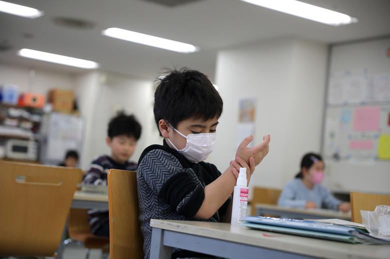 Ребенок, одетый в защитную маску, пользуется дезинфицирующим средством для рук в детском центре Stella Kids, Токио, Япония, 5 марта 2020 года. REUTERS / Стоян Ненов