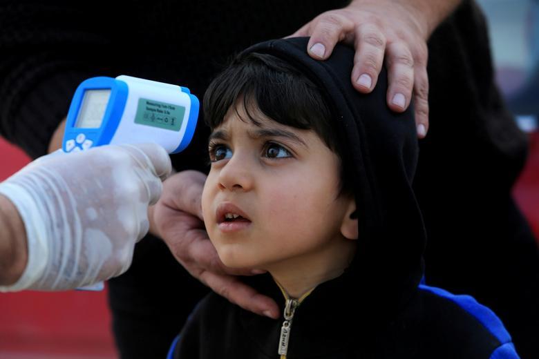 Член медицинской бригады проверяет температуру ребенка на контрольно-пропускном пункте на окраине Духука, Ирак, 2 марта 2020 года. РЕЙТЕР / Ари Джалал