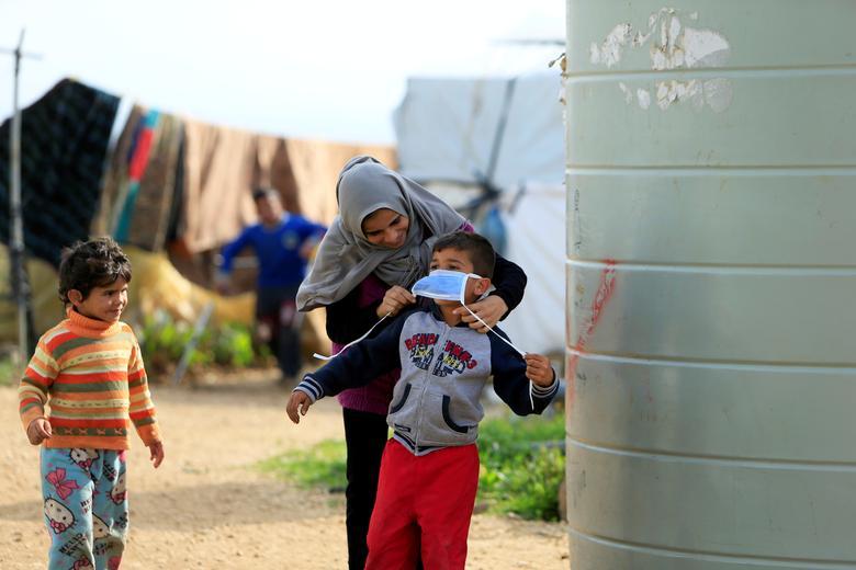 Сирийская женщина-беженка надевает маску на мальчика в районе аль-Ваззани, на юге Ливана, 14 марта 2020 года. РЕЙТЕР / Али Хашишо
