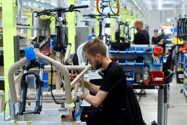 FILE PHOTO: Employees work on electric cargo bicycles at the production plant of e-bike manufacturer Riese & Mueller in Muehltal near Darmstadt,  Germany, August 30, 2019. Picture taken August 30, 2019.  REUTERS/Ralph Orlowski/File Photo