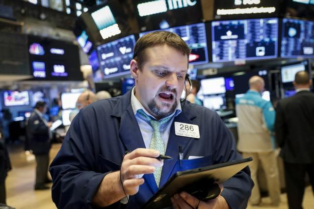 FILE PHOTO: Traders work on the floor of the New York Stock Exchange (NYSE) in New York, U.S., March 20, 2020. REUTERS/Lucas Jackson/File Photo