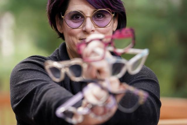 Optician Ali Nelson, jobless after her Washington D.C.-based eyewear store closed due to coronavirus, holds up glasses from her collection at her home in Burke, Virginia, U.S., March 26, 2020.  REUTERS/Kevin Lamarque