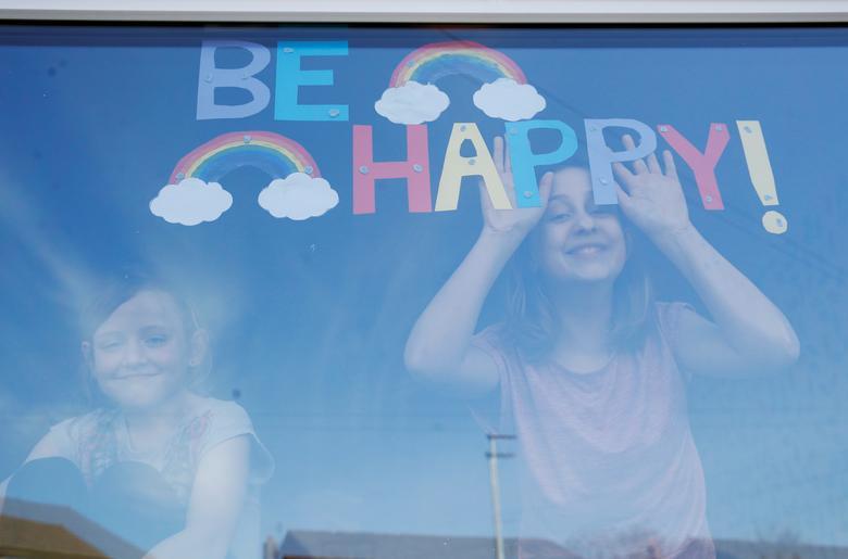 Софі і Емілі Уорд позують для фотографії з мальованої картиною веселок і повідомленням на своєму вікні в Сент-Хеленсі, Великобританія, 25 березня 2020 року. REUTERS / Phil Noble