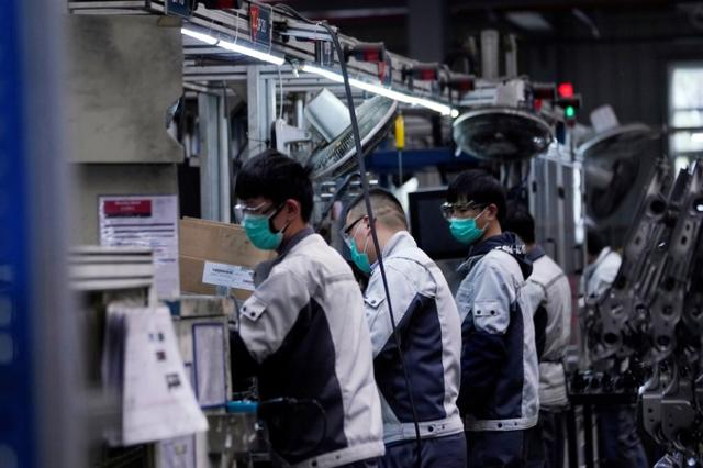 FILE PHOTO: Employees wearing face masks work on a car seat assembly line at Yanfeng Adient factory in Shanghai, China, as the country is hit by an outbreak of a new coronavirus, February 24, 2020. REUTERS/Aly Song