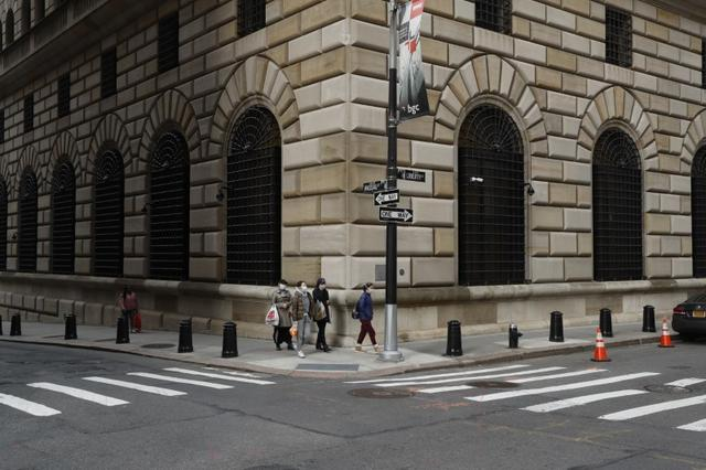 FILE PHOTO: People walk wearing masks outside The Federal Reserve Bank of New York in New York City, U.S., March 18, 2020. REUTERS/Lucas Jackson