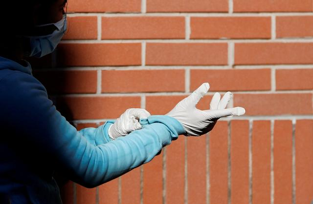 FILE PHOTO: A woman wearing protective face mask and gloves waits for the food distribution organized by the Sant'Egidio Community at San Gaudenzio parish during the lockdown to prevent the spread of coronavirus disease (COVID-19), in Rome, Italy, March 23, 2020. REUTERS/File Photo