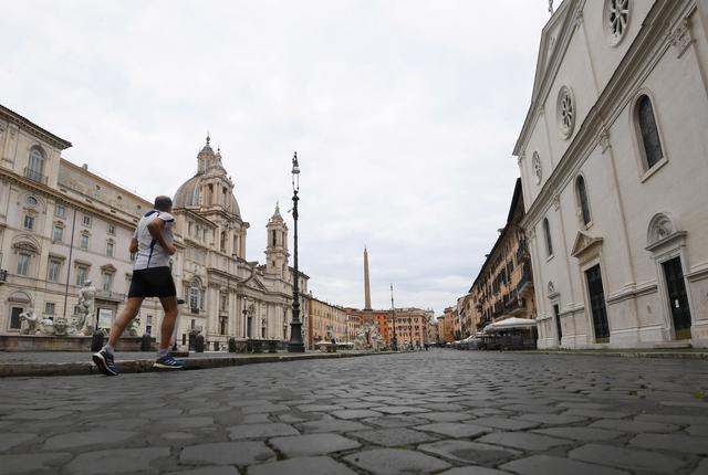 FILE PHOTO: A man jogs at an empty Navona square as Italy tightens measures to try and contain the spread of coronavirus disease (COVID-19), in Rome, Italy March 28, 2020. REUTERS/Alberto Lingria/File Photo