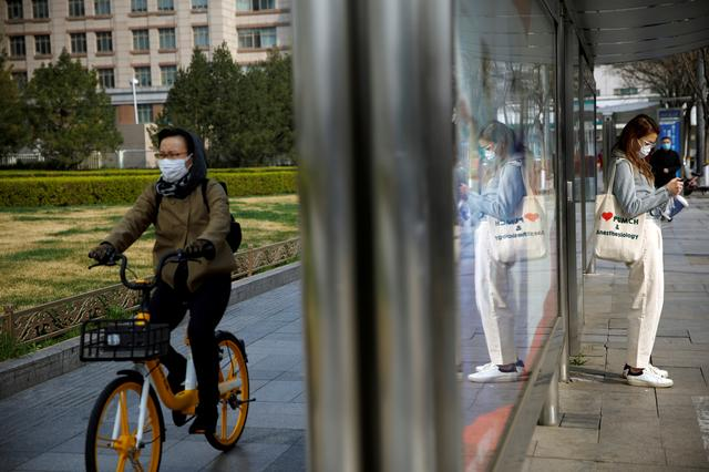 People wear face masks near a bus stop on a street following an outbreak of the coronavirus disease (COVID-19), in Beijing, China March 30, 2020. REUTERS/Carlos Garcia Rawlins