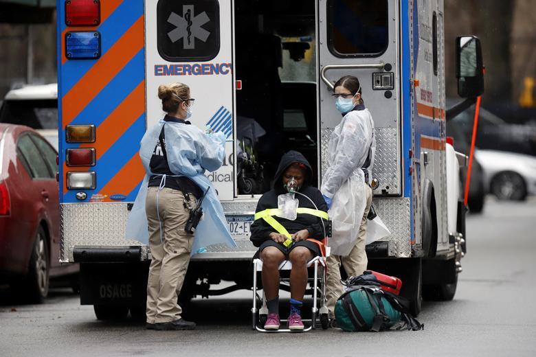 Técnicos de Emergência Médica (EMT), usando equipamentos de proteção, levam um paciente doente a uma ambulância em espera durante o surto de doença por coronavírus na cidade de Nova York, em 28 de março de 2020. REUTERS / Stefan Jeremiah