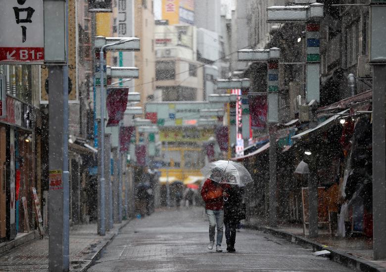Um casal usando máscaras protetoras caminha em uma rua quase vazia no distrito de compras e diversão de Ameyoko, em Tóquio, Japão, em 29 de março de 2020. REUTERS / Issei Kato