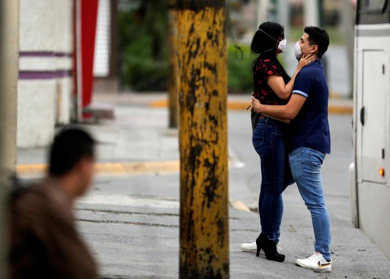 Um casal usando máscaras se abraça em Escobedo, nos arredores de Monterrey, México, em 29 de março de 2020. REUTERS / Daniel Becerril