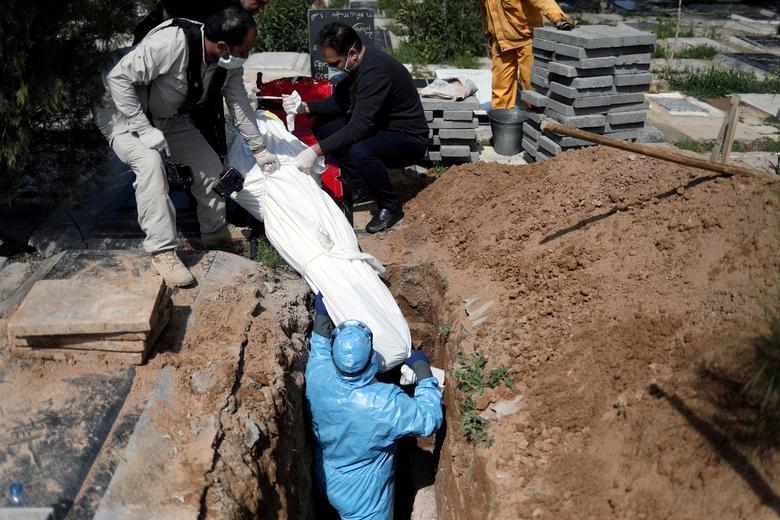 Иранские мужчины хоронят журналиста Абдоллу Завие, который скончался из-за коронавируса, на кладбище Бехешт Захра в Тегеране, Иран, 24 марта 2020 года. WANA (Агентство новостей Западной Азии) / Али Хара через REUTERS