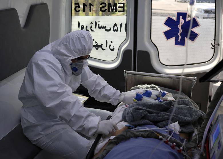 Сотрудник службы скорой медицинской помощи сидит в машине скорой помощи во время передачи пациента с коронавирусом в больницу имени Масиха Данешвари в Тегеране, Иран, 30 марта 2020 года. WANA (Агентство новостей Западной Азии) / Али Хара через REUTERS
