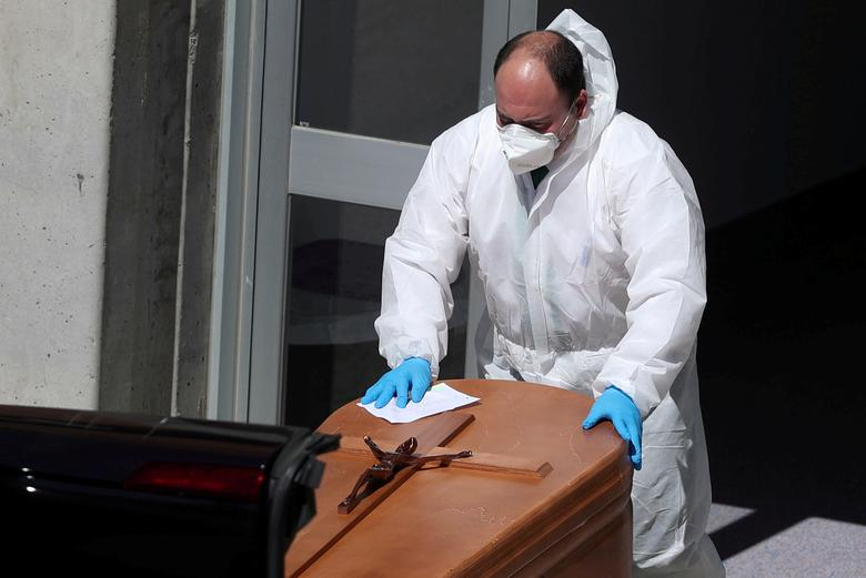 Рабочий на похоронах в защитном костюме выносит гроб из морга в больнице Северо Очоа в Леганесе, Испания, 26 марта 2020 года. REUTERS / Susana Vera