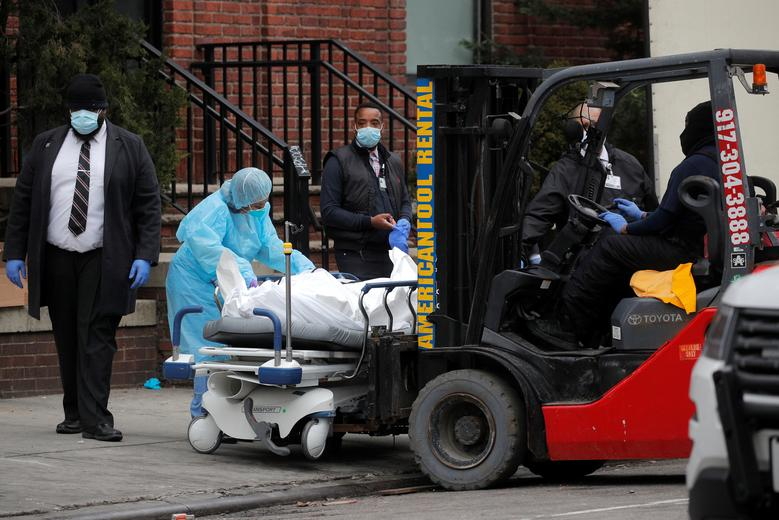 Workers prepare to load a deceased person into a trailer outside of Brooklyn Hospital Center in Brooklyn, March 30, 2020. REUTERS/Brendan Mcdermid