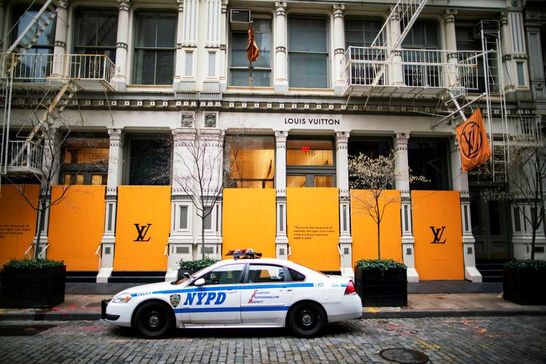A NYPD car is parked in front of a Louis Vuitton store covered up with plywood windows and entrances to prevent looting in New York City, March 31, 2020 REUTERS/Eduardo Munoz
