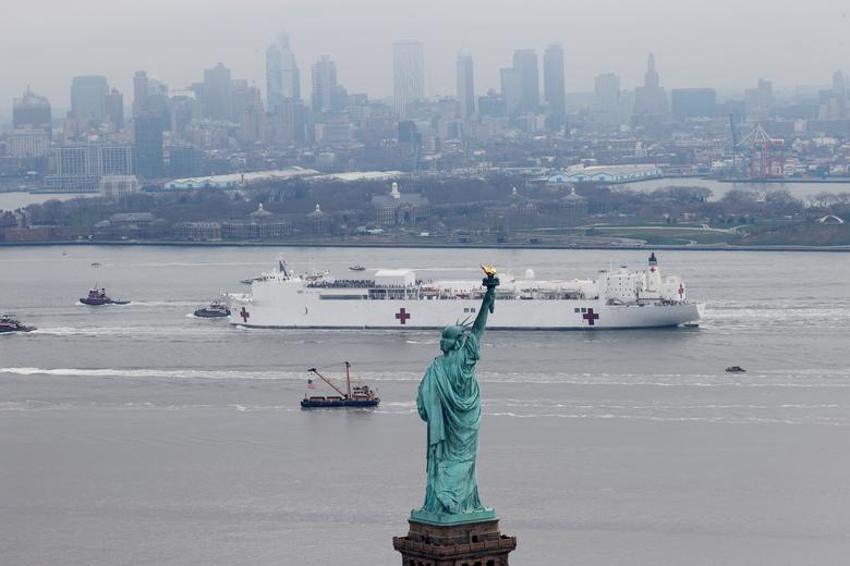 The USNS Comfort passes the Statue of Liberty as it enters New York Harbor in New York City, March 30, 2020. REUTERS/Mike Segar
