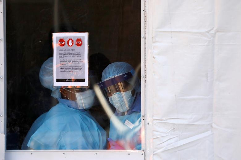 Health workers in protective gear peer from a tent which was constructed to test people for coronavirus outside the Brooklyn Hospital Center in Brooklyn, New York City, March 27, 2020. REUTERS/Andrew Kelly