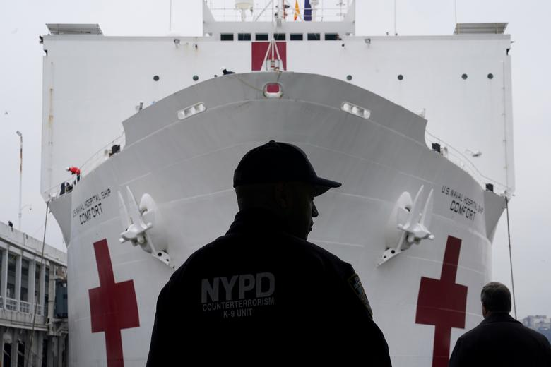 An NYPD officer is pictured as the USNS Comfort pulled into a berth in Manhattan, March 30, 2020. REUTERS/Carlo Allegri