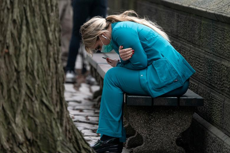 A healthcare worker sits on a bench near Central Park in the Manhattan, New York City, March 30, 2020. REUTERS/Jeenah Moon