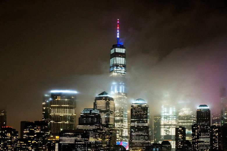 The One World Trade Center is illuminated in red, white and blue in recognition of the nationwide effort to combat coronavirus in New York City, as seen from Exchange Place, New Jersey, March 30, 2020. REUTERS/Eduardo Munoz