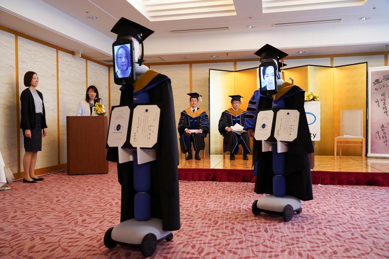 Ipads, прикрепленные к роботам «newme», заменяющим присутствие выпускников на церемонии, носят выпускные платья и шляпы в Токио, Япония, 28 марта 2020 года. BBT UNIVERSITY / Раздаточный материал через REUTERS