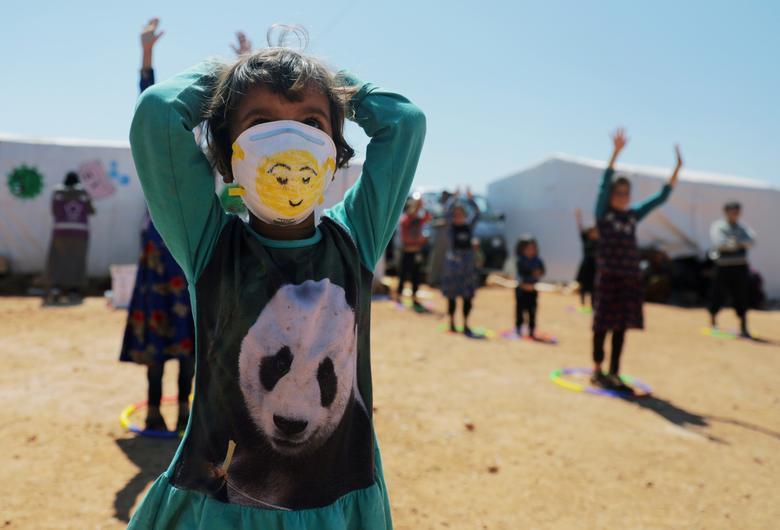 Переміщена дівчина носить лицьову маску, коли бере участь в заході, організованому Violet Organization, з метою поширення інформації та забезпечення безпеки в умовах побоювань, пов'язаних з коронавирусной хворобою (COVID-19), в таборі в місті Маарат-Масрін на півночі Ідліб. , Сирія, 14 квітня 2020 року. РЕЙТЕР / Халіл Ашаві & nbsp;