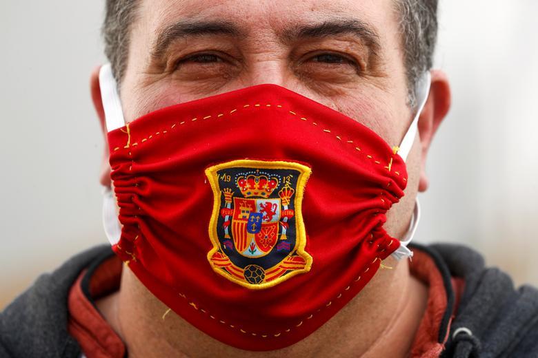 Чоловік позує для знімка, надягаючи захисну маску з гербом іспанської національної футбольної сорочки під час блокування в Ронде, на півдні Іспанії, 13 квітня 2020 року. РЕЙТЕР / Джон Наска
