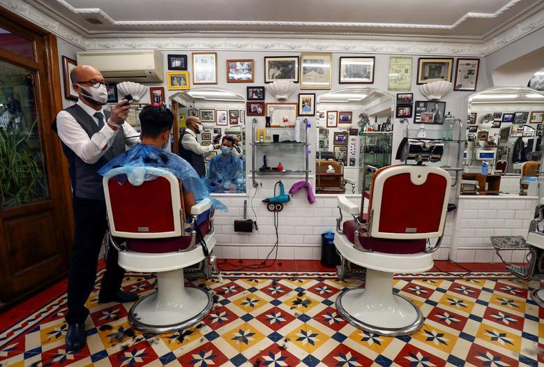 Парикмахер подстригает парикмахерскую в старейшем парикмахерском салоне Мадрида в первый день его открытия в Мадриде, Испания, 4 мая. REUTERS / Sergio Perez & nbsp; & NBSP;